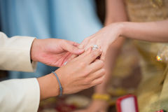 The groom wearing wedding ring for his bride Stock Images