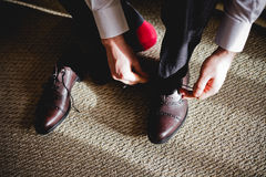 The groom wears black shoes in the hotel Royalty Free Stock Photos