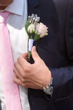 Groom wears boutonniere of roses on his jacket before the wedding ceremony Stock Image