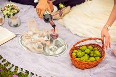 Groom wears bride a glass of wine Stock Photo