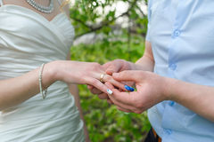 Groom wears bride a gold ring on his finger in the garden Stock Photos