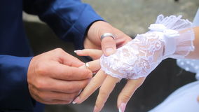 Groom wears on the bride's finger a ring. HD stock video footage