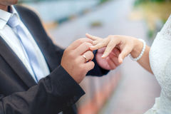 Groom wears bride a wedding ring on his finger. A couple betroth. Ed in the street. Wedding ceremony - hands closeup Royalty Free Stock Photography