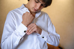Groom wears cuff links on white shirt Royalty Free Stock Photos