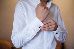 Groom wears cuff links on white shirt Royalty Free Stock Photo