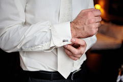 Groom wears cufflinks for shirt.  Royalty Free Stock Images