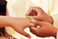 Groom wears a diamond ring onto the brides hand Royalty Free Stock Image