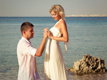 Groom wears ring bride on beach Stock Images