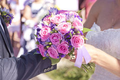 The groom wears a ring bride. The groom wears the ring bride, brides bouquet selective focus Stock Image
