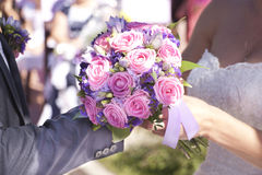The groom wears a ring bride. The groom wears the ring bride, brides bouquet selective focus Stock Photos