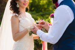 Groom wears ring on bride`s finger Stock Image