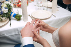 The groom wears ring bride. Wedding ceremony. Ring of white and yellow gold Royalty Free Stock Image