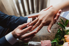 The groom wears the ring bride. Wedding ceremony. Ring of white and yellow gold Royalty Free Stock Photography