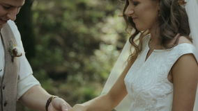 Groom wears the ring on the finger of the bride stock footage
