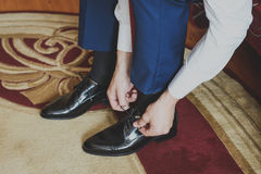 Groom wears shoes. Business style. Royalty Free Stock Photography