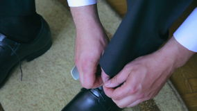 The groom wears shoes, tying laces, closeup stock video footage