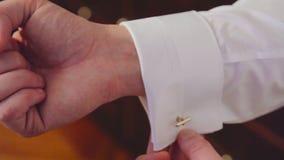 Groom wears stylish cufflinks close up stock video