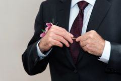 The groom wears a suit in front of a mirror Royalty Free Stock Photo