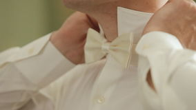 The groom wears for a wedding, puts bow-tie stock video footage
