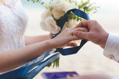 The groom wears a wedding ring on the finger of the bride close-up Stock Image
