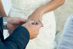 The groom wears a wedding ring on the finger of the bride close-up Royalty Free Stock Photography