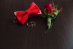 Groom wedding accessories. Red Boutonniere, gold rings and bow-tie on brown background Royalty Free Stock Photo