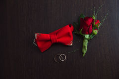 Groom wedding accessories. Red Boutonniere, gold rings and bow-tie on brown background Royalty Free Stock Images