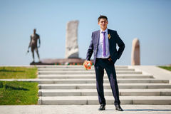 Groom with wedding bouquet on background of monument to soldiers. Stock Photo