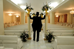 Groom in wedding chapel. Groom wearing morning suit walking down empty aisle of wedding chapel, rear view Stock Images