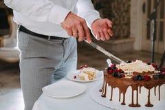 Groom cut wedding cake royalty free stock photo