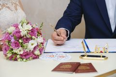 The groom on a wedding day puts a signature. Wedding ceremony royalty free stock image