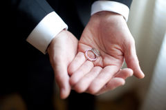 Groom with wedding ring. Closeup of groom holding wedding rings in hands Royalty Free Stock Photography