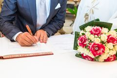 Groom during the wedding signature. Groom sign on registration of marriage during your wedding day Stock Images