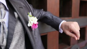 Groom in wedding suit with flower snaps fingers stock video footage