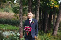 Groom at wedding tuxedo smiling and waiting for bride. Groom at wedding tuxedo with bouquet smiling and waiting for bride. Elegant groom in costume and bow-tie Stock Photos