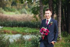 Groom at wedding tuxedo smiling and waiting for bride. Elegant groom in costume and bow-tie Royalty Free Stock Image
