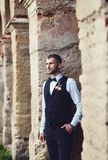 Groom at wedding tuxedo smiling and waiting for bride. Near brick buildingl. Elegant groom in costume and bow-tie Royalty Free Stock Photo