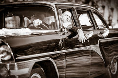 Groom at a wheel of a black old retro of the car Royalty Free Stock Photography