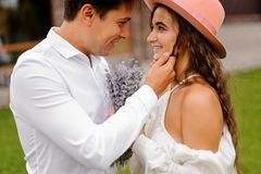Groom in white shirt and beautiful bride in white dress lovingly looking at each other. Handsome groom in white shirt and beautiful bride in white dress with Royalty Free Stock Photo