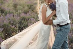 Groom in a white shirt and a bride in a dress of white color in a lavender field with a bouquet of lavender royalty free stock image