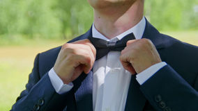 The groom in a white shirt puts on  bow tie from the front, outdoor, closeup. Royalty Free Stock Photography