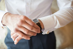 The groom in white shirt puts on a watch, close-up Royalty Free Stock Images