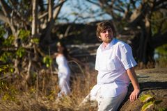Groom in a white shirt sits in the middle of tropical plants, and behind him is the bride stock photo