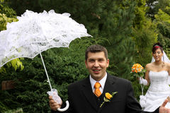 Groom with white sunshade. Bride quarrying the smiling groom royalty free stock images