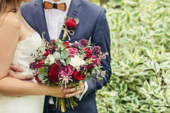 Groom with wooden bow-tie and red boutonniere hug bride with lil. Ac wedding bouquet Royalty Free Stock Images