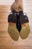 A groom with the words help on the bottom of his shoes. Royalty Free Stock Photos