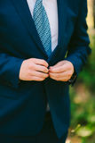 The groom zips up the jacket. The wedding dress Stock Photography