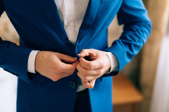 The groom zips up the jacket Stock Images