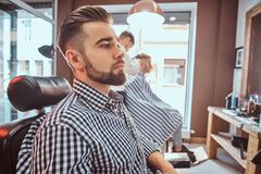 Groomed handsome man is waiting for his turn to get a haircut at busy barbershop. Groomed handsome men is waiting for his turn to get a haircut at busy royalty free stock photos