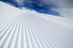 Groomed ski slope. Morning view of a ski slope with fresh tracks of the snow groomer Stock Photo